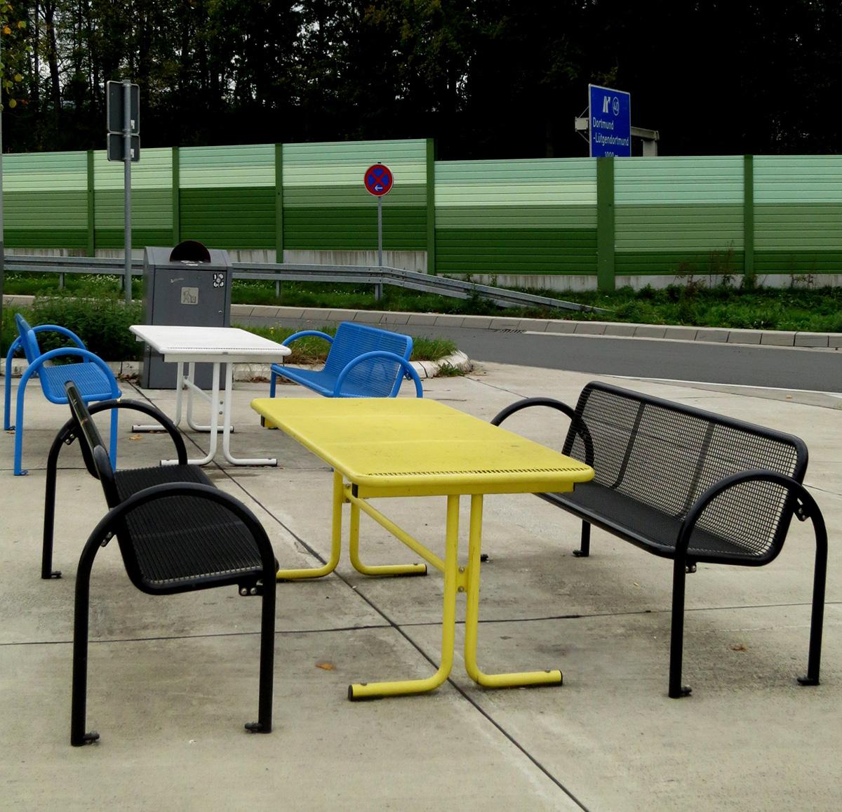 Eine Autobahnraststätte mir blauen Bänken und einem weißen Tisch sowie schwarzen Bänken und einem gelben Tisch in der Nähe von Dortmund
