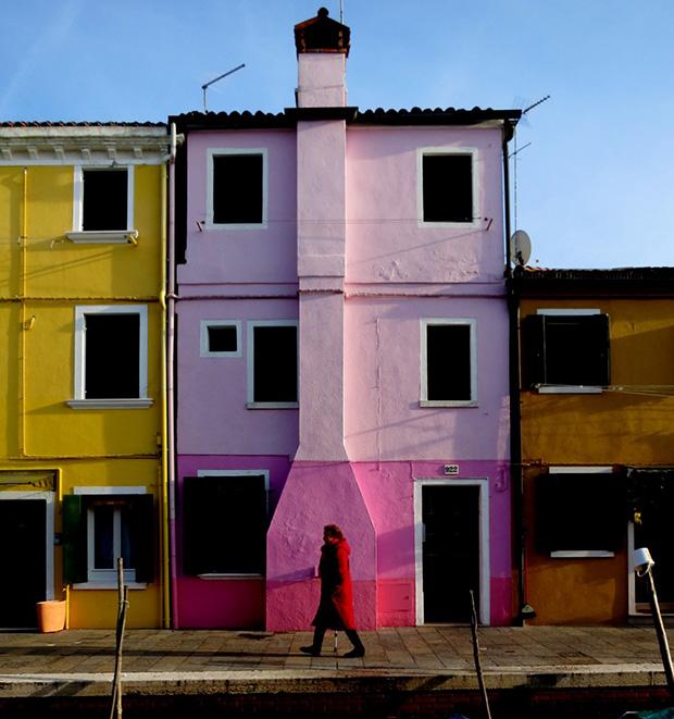 Farbige Häuserzeile auf Burano – gelb, rosafarben, ocker, davor eine Frau im roten Mantel