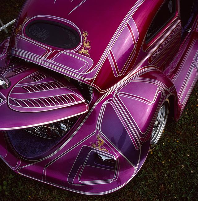 Ein in Pink-, Rose- und Rottönen lackierter VW Käfer